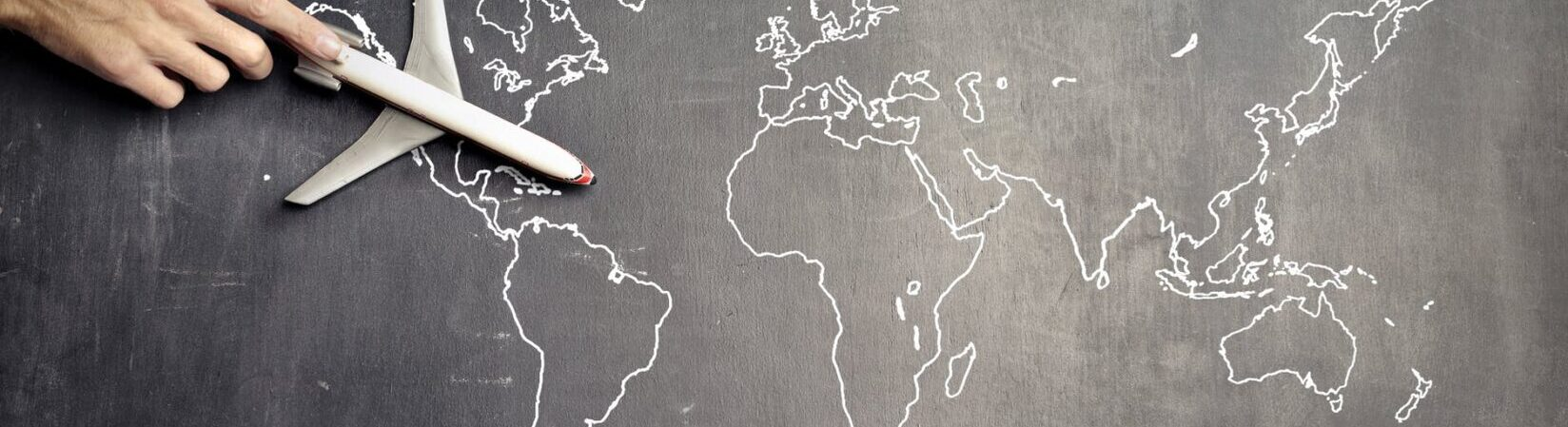 miniature airplane and hand of person over drawn map